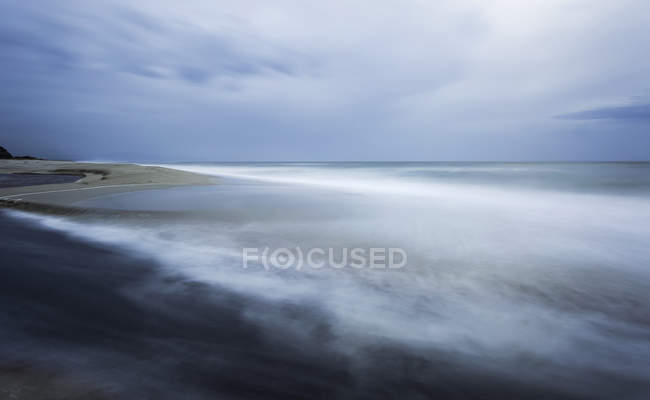 Tranquil sea water with some mist against sandy shore  during daytime — Stock Photo