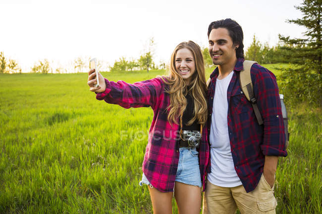 Happy couple standing on green grass field and making selfie on smartphone — Stock Photo