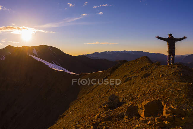 Man standing on mount top with arms outstretched against sun — Stock Photo