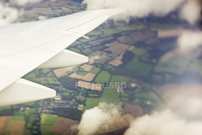 Vista parcial del ala del avión volando sobre la aldea con campo verde durante el día - foto de stock