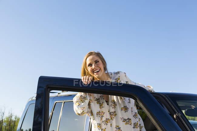 Glücklich lächelnde Frau stützte sich auf die geöffnete Tür des Autos — Stockfoto