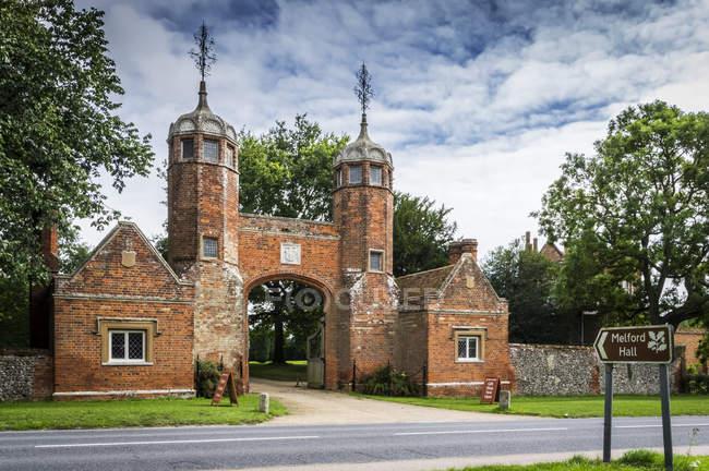 Вигляд церкви з вежами і arch вхід під хмарного неба, Melford зал, Великобританія — стокове фото