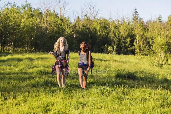 Deux filles heureuses marchant sur l'herbe dans la forêt pendant la journée — Photo de stock