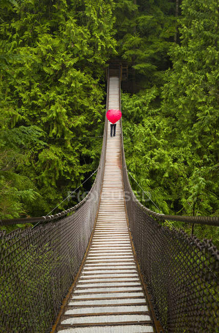Woman With A Red Heart-Shaped Umbrella Crossing The Lynn Canyon Suspension Bridge, North Vancouver; Vancouver, British Columbia, Canada — Stock Photo