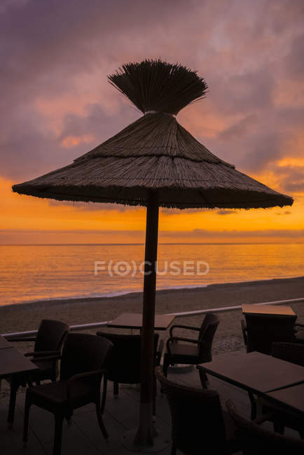Un ombrello Thatch su un tavolo con sedie sulla spiaggia al tramonto, con vista sul Mar Mediterraneo; Mentone, Costa Azzurra, Francia — Foto stock