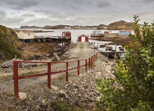 Blick auf roten Zaun am Ufer gegen Wasser und Gebäude am Wasser — Stockfoto