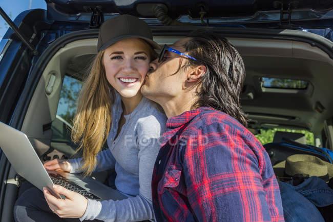 Lächelnde Frau mit Mütze und Laptop in der Hand, die am Auto sitzt, während Mann sie küsst — Stockfoto