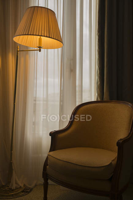 A Floor Lamp Illuminated Beside A Chair And Window; Cannes, Cote D'azur, France — Stock Photo