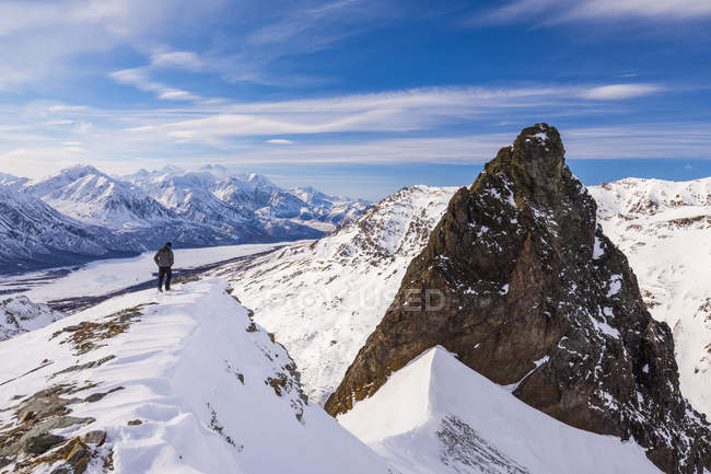 Lone man standing on edge of mountain peak covered with snow — Stock Photo