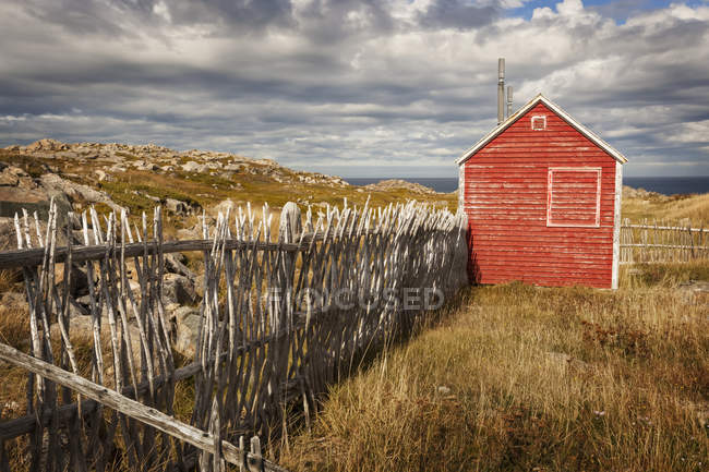 Vecchio fienile rosso in legno e recinzione sul campo con piante, erba e pietre sotto il cielo nuvoloso — Foto stock