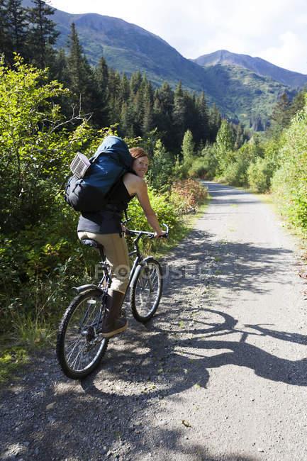 A Woman Mountain Bikes Down A Trail In A Forest With A Backpack; Alaska, Estados Unidos da América — Fotografia de Stock