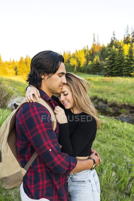 Молодая влюбленная пара, стоящая на поле и обнимающая друг друга на заднем плане — стоковое фото
