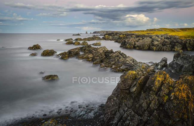 Скелястий берег з валунами над морською водою під хмарного неба — стокове фото