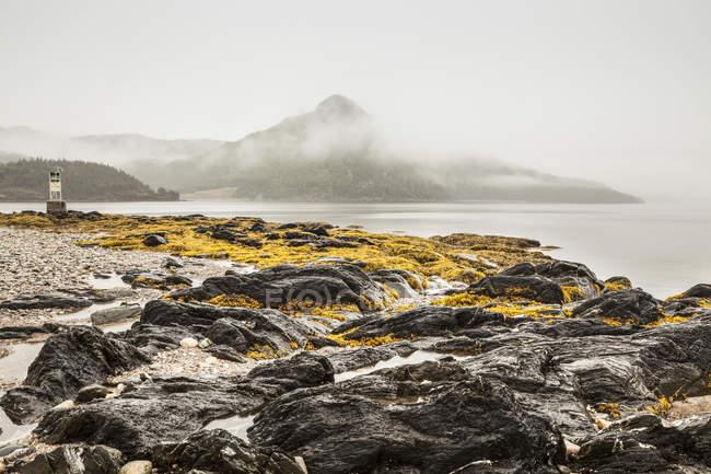 Перегляд скелястий берег проти морської води з пагорбів на тлі — стокове фото