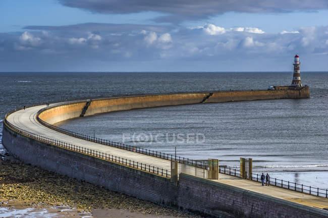 Vue de la jetée avec phare sur l'eau de mer pendant la journée — Photo de stock