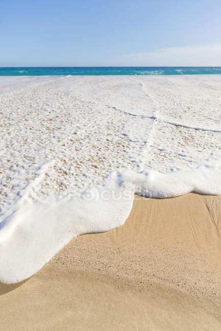 Переходячи піщані пляжі і чисте синє води на фоні води — стокове фото