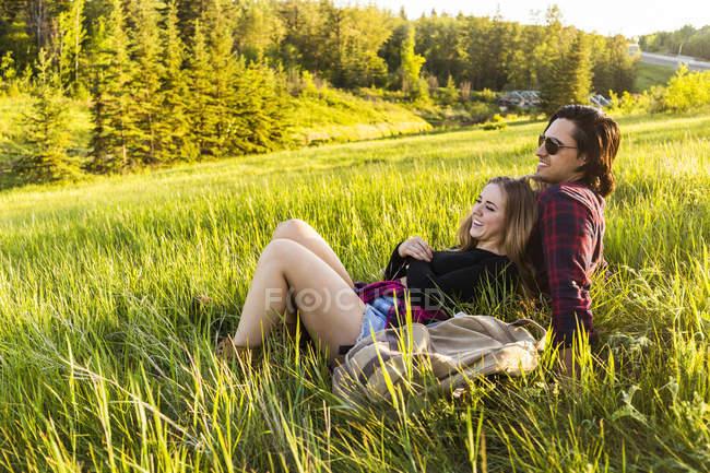 Couple romantique posé sur l'herbe verte sur le champ avec des arbres sur le fond tout en s'embrassant — Photo de stock