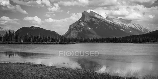 Imagem de preto e branco de água e neve coberto de picos de montanhas sob céu nublado — Fotografia de Stock
