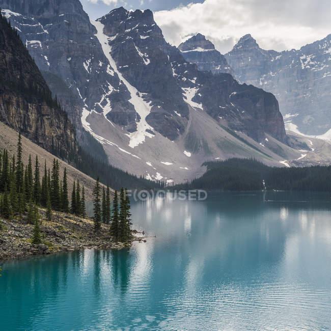 Спокойное горное озеро с деревьями на берегу и горные склоны со снегом в дневное время — стоковое фото
