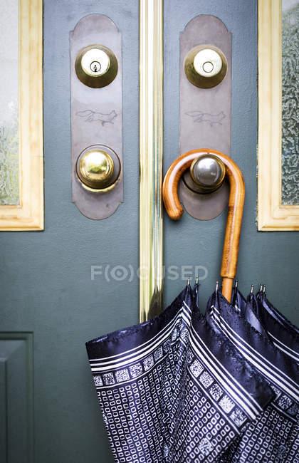 Regenschirm, der an einer Türklinke hängt; surrey, britisch columbia, canada — Stockfoto