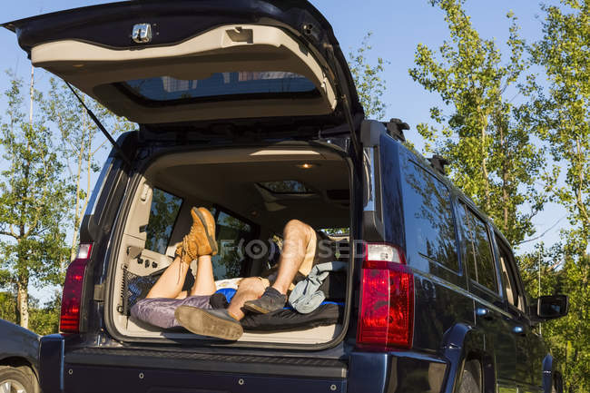 View of couple laying at car outdoors during daytime — Stock Photo