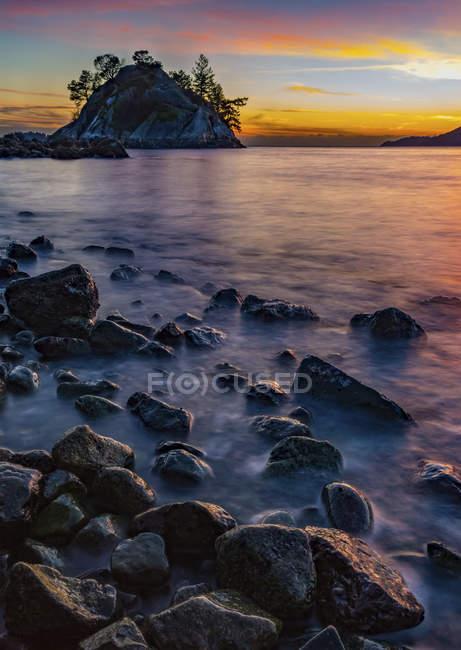 Золотой солнечный свет, освещающий облака вдали и мокрые камни вдоль короткой линии; Ванкувер, Британская Колумбия, Канада — стоковое фото