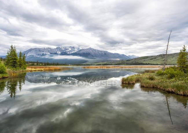 See-Reflexionen und die Rocky Mountains in der Nähe von Jasper in den frühen Morgenstunden, Jasper-Nationalpark; Alberta, Kanada — Stockfoto