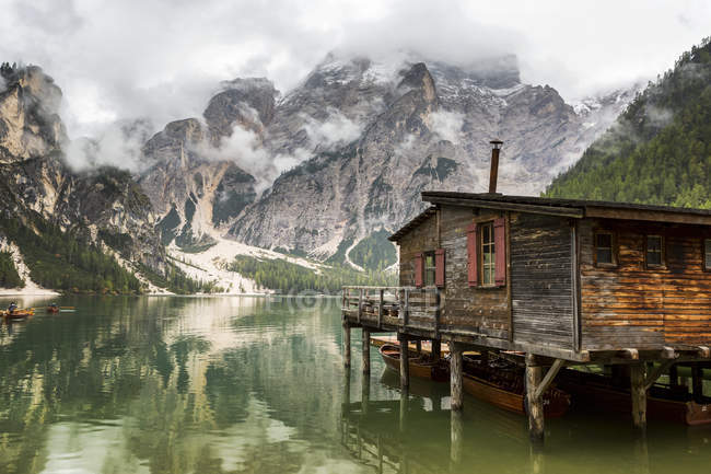 Wooden lake boat house with misty clouded mountain in the background and lake reflection; Sesto, Bolzano, Italy — Stock Photo