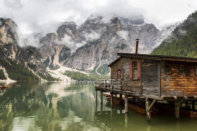 Лодочный домик на озере Вуден с туманной мутной горой на заднем плане и озером; Сесто, Больцано, Италия — стоковое фото