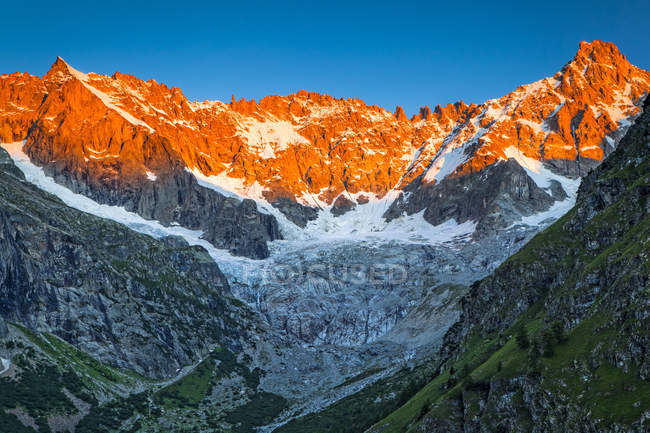 Sunrise glow on the peaks above l'A Neuve Glacier, viewed from La Fouly, Swiss Val Ferret, Alps; La Fouly, Val Ferret, Switzerland — Stock Photo