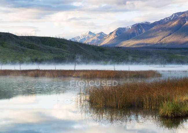 Mist rising over an alpine lake in the early morning, Jasper National Park; Jasper, Alberta, Canada — Stock Photo