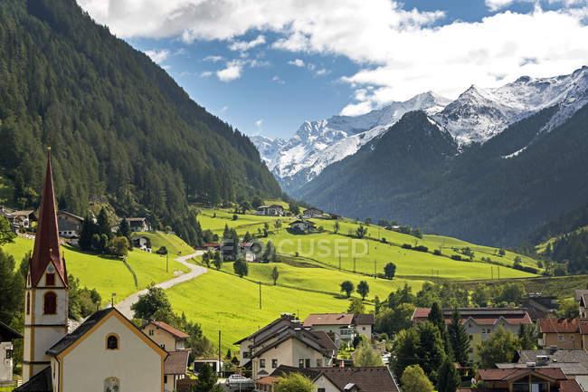 Альпийская деревня с церковной колокольни, зеленые луга в долине и снегом покрыты горы на расстоянии; St. Jodok, Тироль, Австрия — стоковое фото