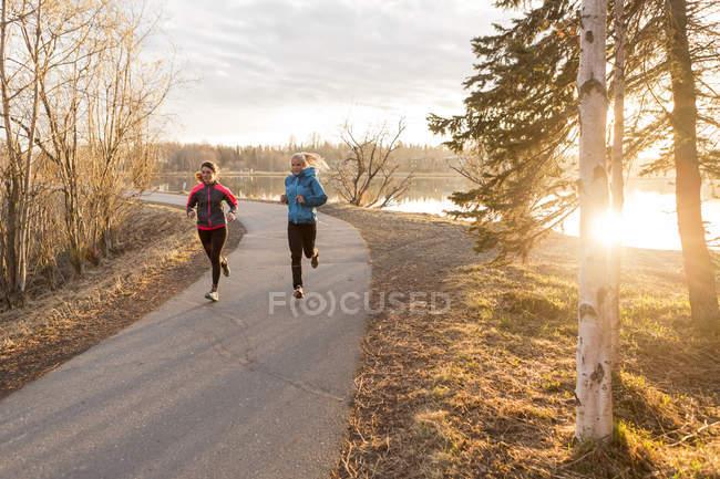 Duas jovens mulheres correndo em uma trilha na beira da água; Anchorage, Alasca, Estados Unidos da América — Fotografia de Stock