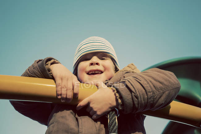 Portrait of a young boy playing on playground equipment — Stock Photo