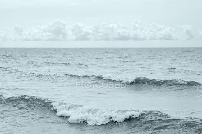 Onde diagonale per l'immagine e una banda di piccoli cumuli di galleggiamento proprio sopra l'orizzonte; Ontario, Canada — Foto stock