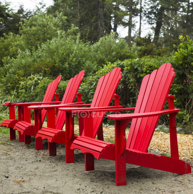 Quatro cadeiras Adirondack vermelhas em uma fileira em Chesterman Beach, Vancouver Island, Pacific Rim; Tofino, British Columbia, Canadá — Fotografia de Stock