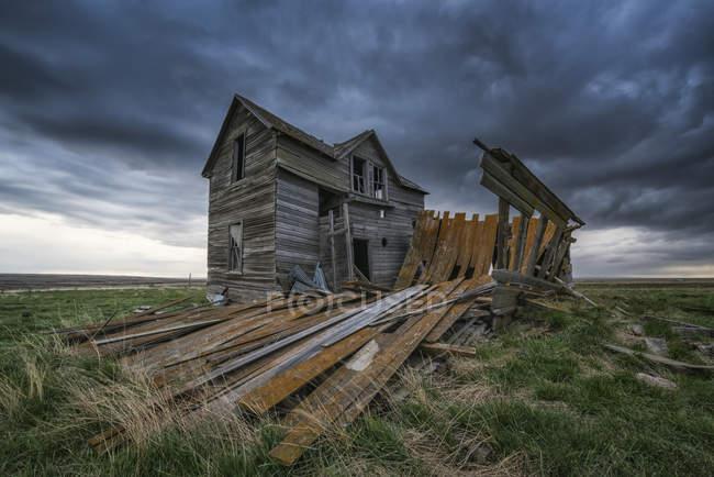Casa abbandonata sulle praterie con nuvole di tempesta sopra al tramonto; Val Marie, Saskatchewan, Canada — Foto stock