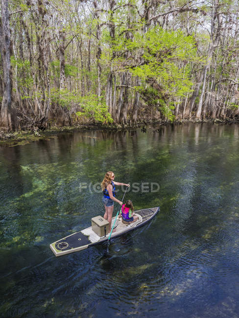 Мать и дочь paddleboard вниз по течению пресноводные весны; Chiefland, Флорида, Соединенные Штаты Америки — стоковое фото