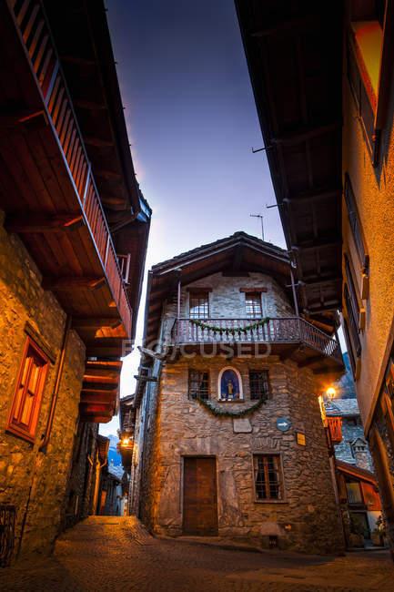 Старые каменные здания и старинные мощеные улицы, освещаемые в сумерках, Долонне, недалеко от Курмара, долина Аоста, Италия — стоковое фото