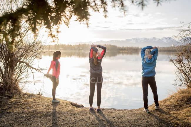 Три молодые женщины, растянувшиеся по тропе на краю воды; Анкоридж, Аляска, США — стоковое фото