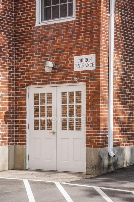Puertas en una pared de ladrillo de un edificio de la iglesia con el cartel encima de la lectura 'Entrada de la iglesia'; Connecticut, Estados Unidos de América - foto de stock