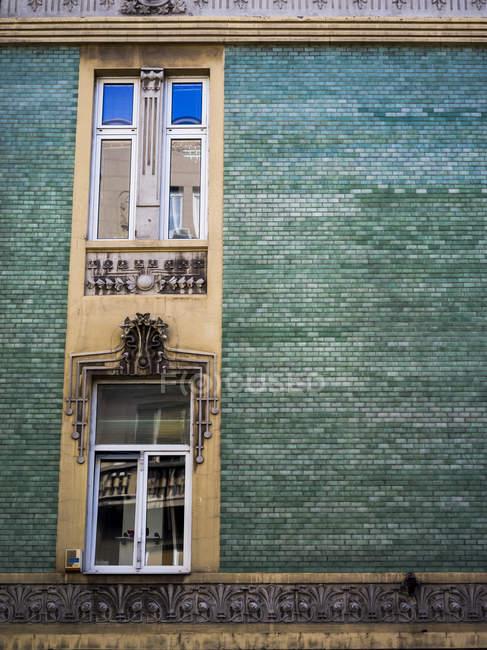 Un bâtiment avec briques vertes et fenêtres avec décor orné ; Belgrade, Voïvodine, Serbiade — Photo de stock