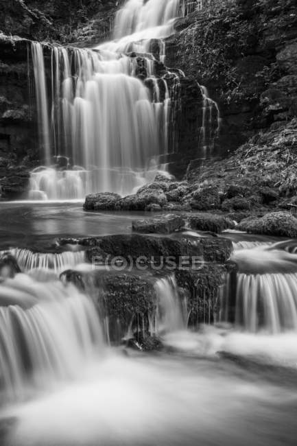 Black and white image of numerous waterfalls flowing over rocks in the Yorkshire Dales; Settle, North Yorkshire, England — Stock Photo