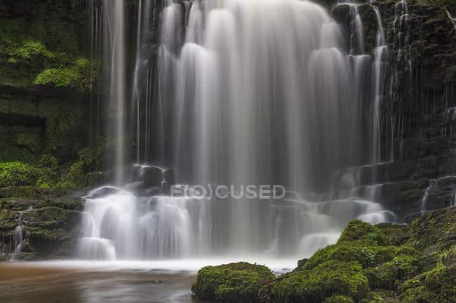 Numerosas cascadas que fluyen sobre rocas en una piscina en Yorkshire Dales; Settle, North Yorkshire, Inglaterra - foto de stock