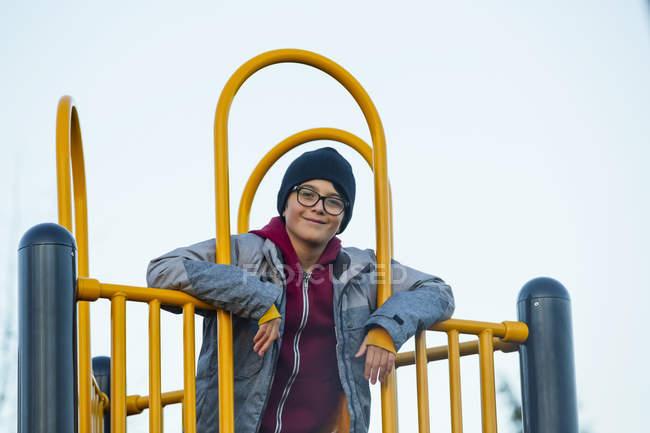 Portrait d'un jeune garçon jouant sur un équipement de terrain de jeu — Photo de stock