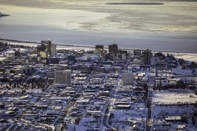 Вид с воздуха на 3-й, 4-й, 5-й и 6-й авеню, идущие на запад к океану через центр Анкориджа, морской лед на заливе Кука на заднем плане, отели Marriot, Hilton и Captain Cook на переднем плане, Юго-Центральная Аляска — стоковое фото