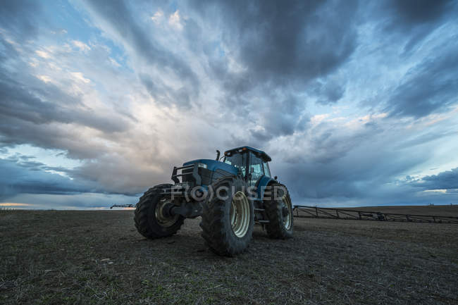 Tracteur stationné dans un champ sous un ciel dramatique au coucher du soleil; Val Marie (Saskatchewan), Canada — Photo de stock
