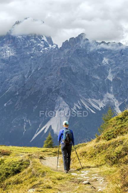 Randonneuse sentier alpin avec cloud couvert de montagnes à l'arrière-plan, Sesto, Bolzano, Italie — Photo de stock