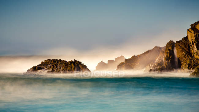 Mist over the turquoise water along the rugged coastline; Big Sur, California, United States of America — Stock Photo