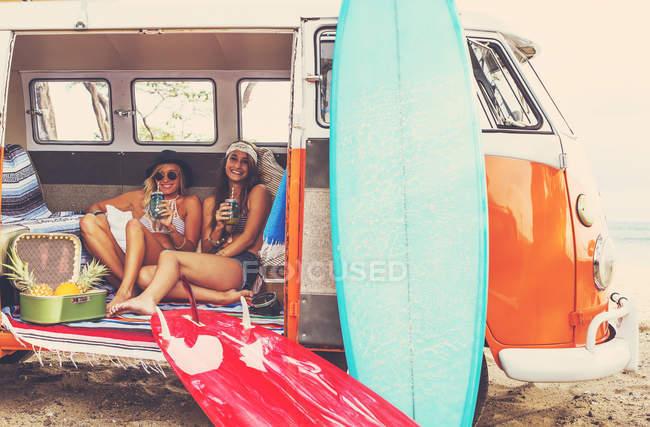 Estilo de vida na praia. Meninas Surfistas Bonitas se divertindo saindo em Surf Van Vintage. Melhores amigos . — Fotografia de Stock